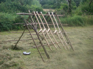 Scythes and hay forks safely stored on a hay rack during a scythe course.